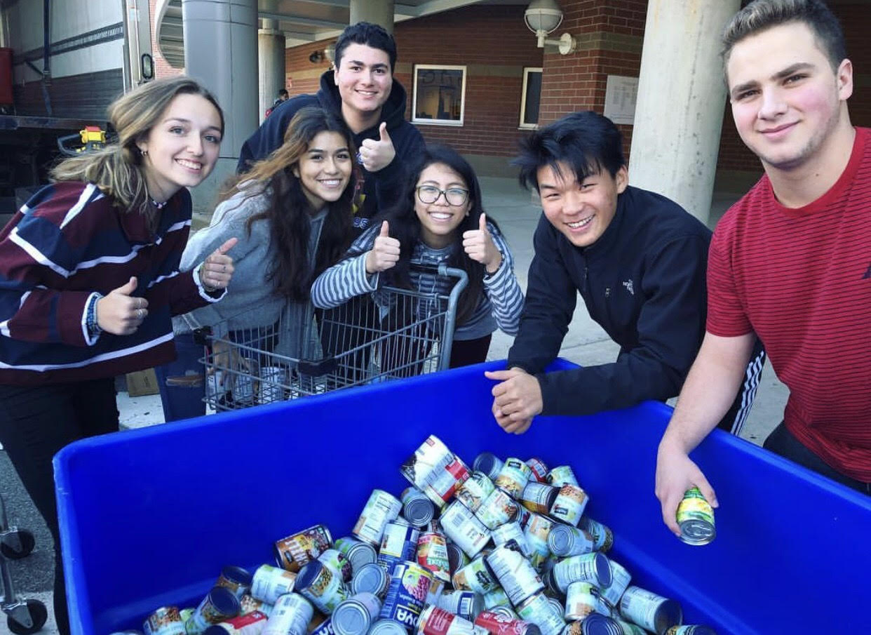 Students prepare to load donated cans onto a Manna Food Center truck.