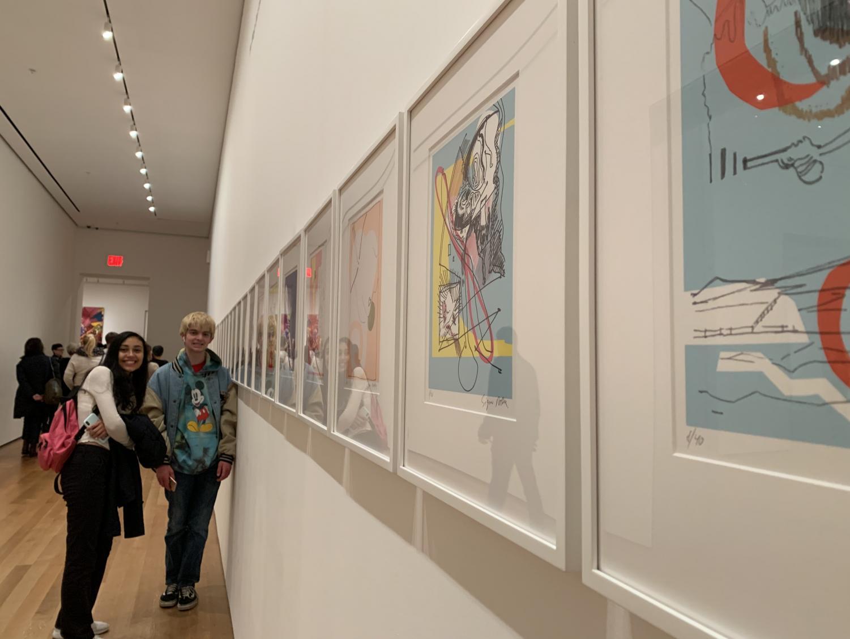 Seniors look at a series of prints at MoMA.