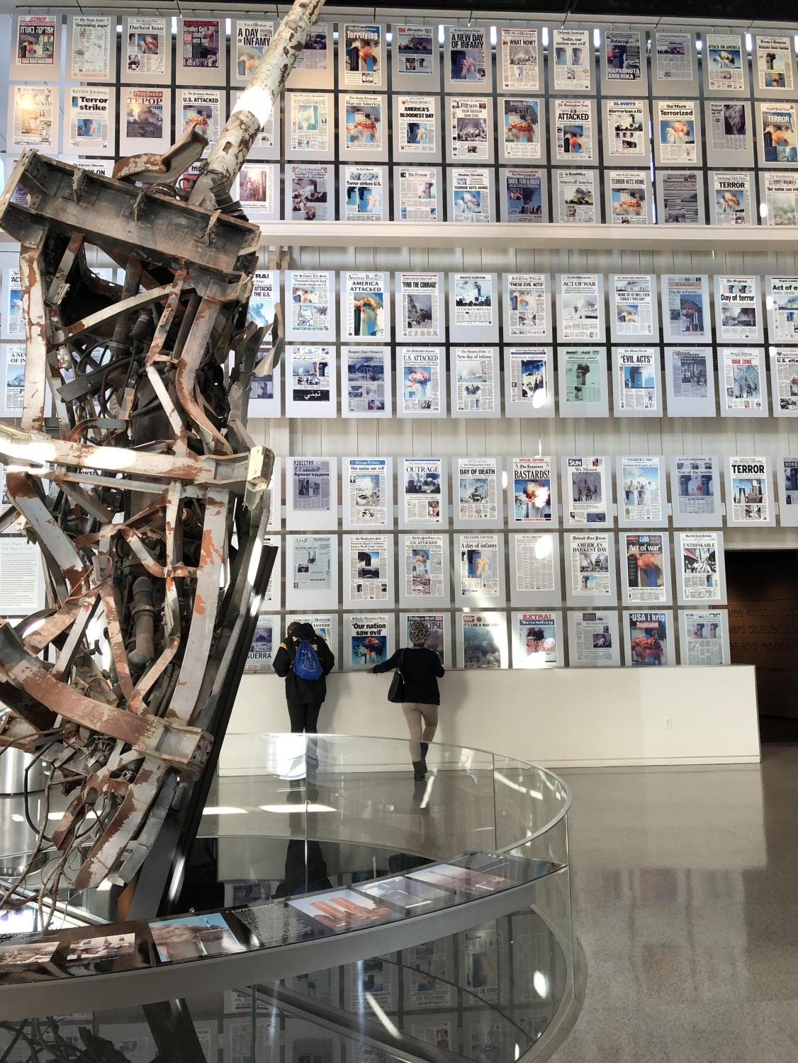 Junior Cory Bucy and senior Crystal Foretia view historic front pages at the 9/11 Gallery.