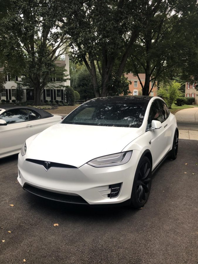 A Tesla electric car is parked on the street.