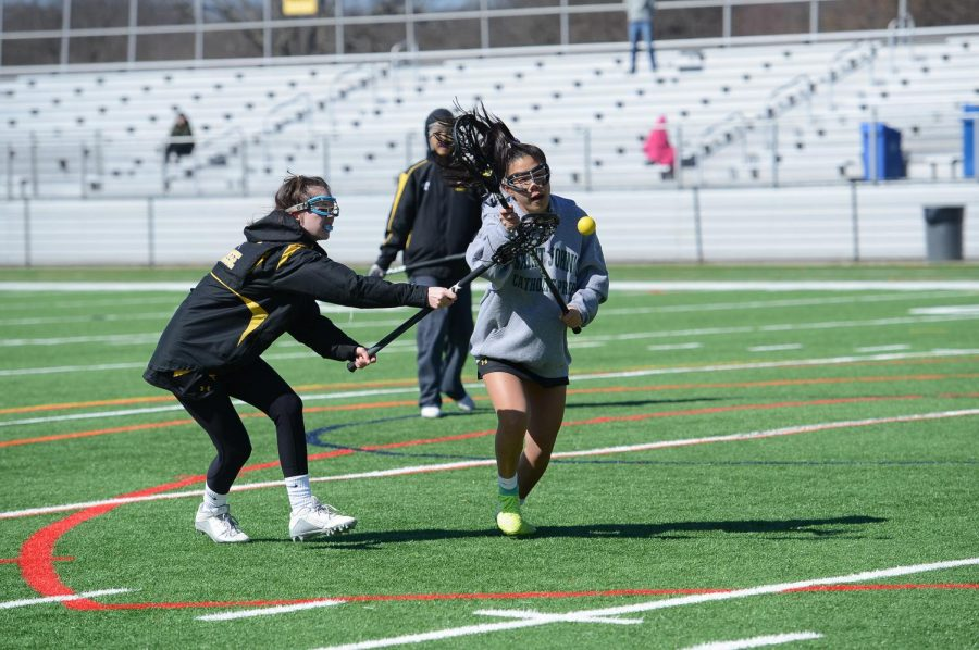 Chang cradles up field as she avoids defenders during lacrosse practice.
