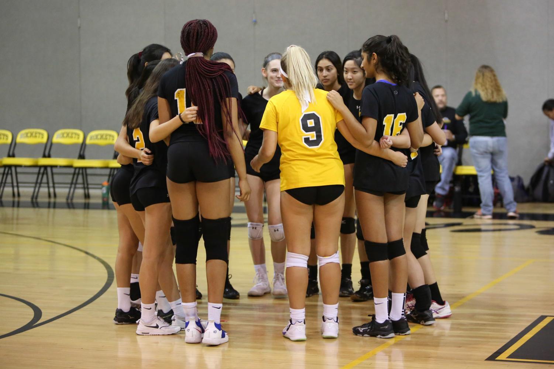Girls volleyball huddles up during their Senior Night game against Gaithersburg.