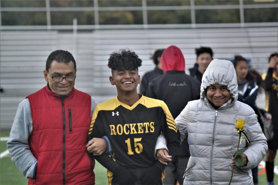 Senior Agustin Diaz walks down the field with his parents during senior night celebration.