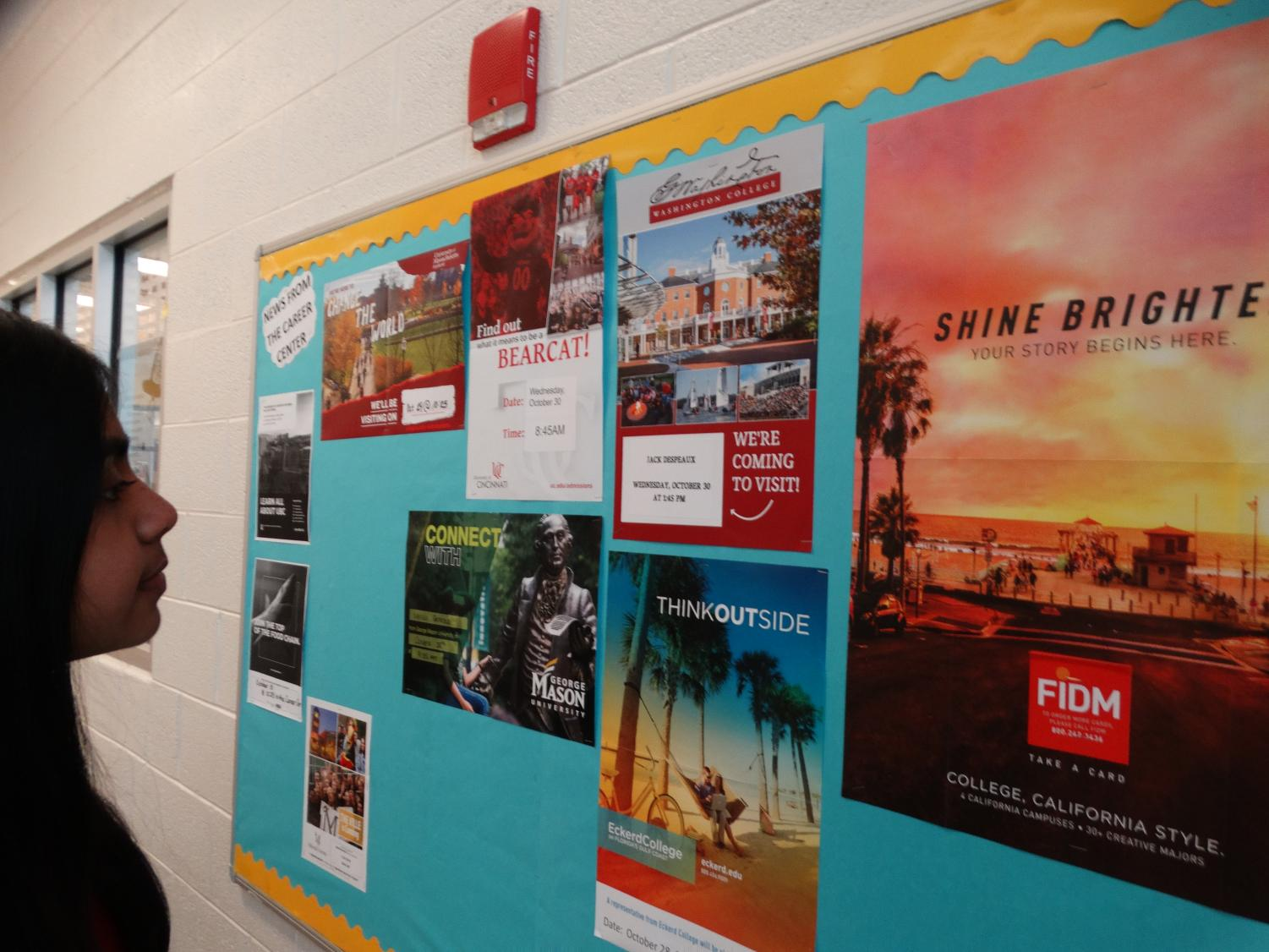 A student examines the different post-high school college options posted on the wall.