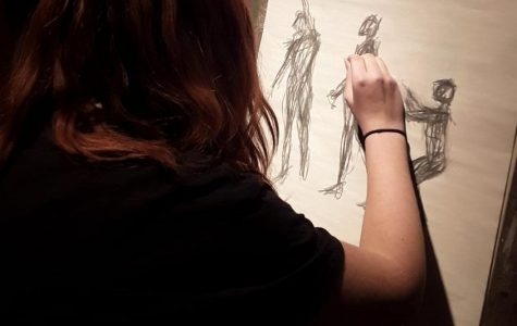 A student completes a live figure study in the AP/IB Art class.