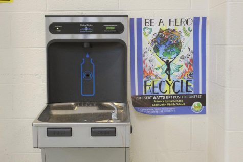 A SERT poster next to an RM water fountain encourages students to maintain green habits.
