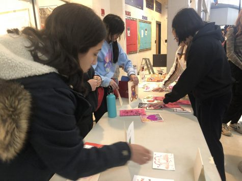 Seniors Ashley Guevara and Gabriella Ceniza prepare for the annual Valentines Day card sale on Main Street, hosted by National Art Honor Society (NAHS). Various members of NAHS will be selling these cards during lunch throughout the week of Feb. 10 to Feb. 15 in order to raise money for their organization.