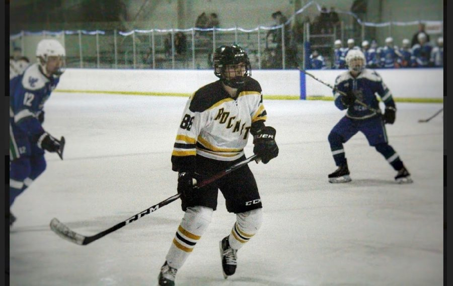 Senior Justin Culp-Gonzalez observes the puck as he skates down the ice.
