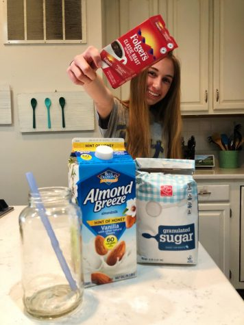 Brooke Hilliard posing with all the ingredients for a perfect cup of whipped coffee