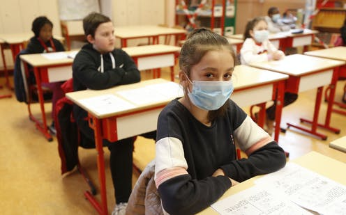 School kids, some wearing masks, attend a class in a school in Strasbourg, France in May 2020.