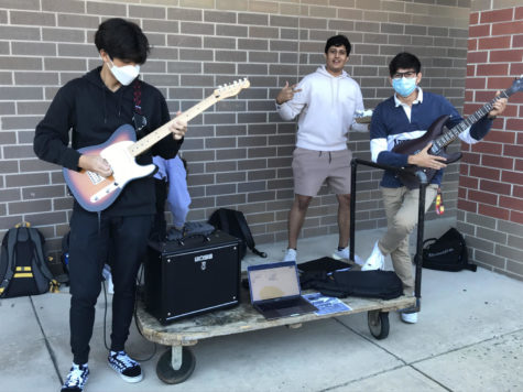 With his guitar out and ready, senior Patrick Kim attempts to recruit students to join the RM Rock & Metal Club (RM-RM) along with two of his friends. This club is where we can get together, listen to fun music, try to learn it together and have fun, Kim said. (Davi Jacobs)